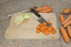 Schneiden von Karotten auf hölzernem Schneidebrett Lizenzfreies Stockbild