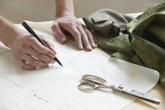 Schneider-Drawing Pattern On-Papier bei Tisch Lizenzfreie Stockbilder