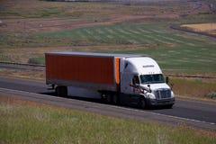 Schneider que acarrea/remolque blanco de la naranja de Freightliner fotos de archivo
