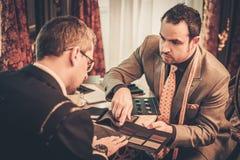 Schneider und Kunde, die Materialien für Anzug wählen Stockfotografie