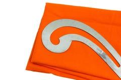 Schneiderausrüstung auf orange Stoff Lizenzfreie Stockfotografie