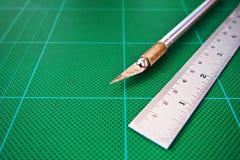 Schneidermesser auf grünem Brett lizenzfreie stockbilder