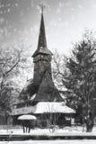 Schneien über einer traditionellen rumänischen hölzernen Kirche Stockfotos