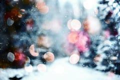 Schneiendes abstraktes Muster mit dem Schneien gegen Winter Wald und bokeh beleuchtet Winter Wald- und bokehlichter Stockfotografie