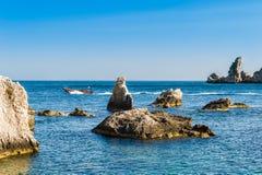Schnellboot und scharfe Felsen nahe Isola Bella stockbilder