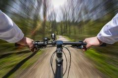 Schnelle Fahrrad-Fahrt durch das Holz Stockfoto