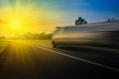 Schnelle Geschwindigkeit des Autos sehr auf der Straße am Abend und am Strahlnsonnenuntergang Unter Verwendung des Ideenhintergru lizenzfreies stockfoto