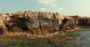 Schneller Flug über dem ruhigen blauen Meer Die Kamera bewegt sich rechts Steinklippe wird mit azurblauem Wasser gewaschen stock video footage