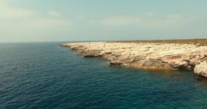 Schneller Flug über dem ruhigen blauen Meer Steinklippe wird mit azurblauem Wasser gewaschen stock footage