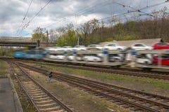 Schneller Güterzug transportiert Autos auf Schienen Stockbilder