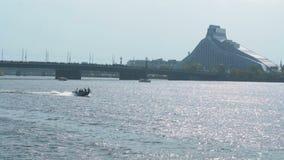 Schneller Schnellbootschneider, der auf den Fluss vor einem modernen Architekturgebäude in Europa im sonnigen Tag des Sommers lau stock footage