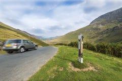Schnelles Auto mit hügeliger Landschaft Stockbild