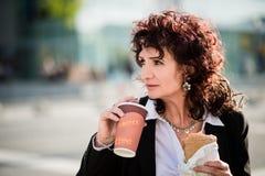 Schnelles Mittagessen - Geschäftsfrau, die in der Straße isst Stockfotografie
