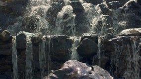 schnelles Stromwasser Schließen Sie oben vom Wasser, das über Steine in der Zeitlupe fällt stock video