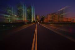 Schnellfahren in Richtung zu einer modernen Stadt an der Dämmerung lizenzfreie stockbilder