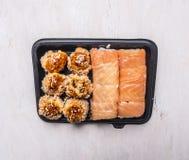 Schnellimbiß der köstlichen Sushi in einem Draufsichtabschluß des Hintergrundes des schwarzen Behälters hölzernen rustikalen oben Lizenzfreie Stockfotos