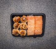 Schnellimbiß der köstlichen Sushi in einem Draufsichtabschluß des Hintergrundes des schwarzen Behälters hölzernen rustikalen oben Lizenzfreies Stockfoto