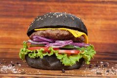 Schnellimbiß, appetitanregender schwarzer Burger, schön ausgebreitet auf einem hölzernen Hintergrund stockbild