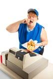 Schnellimbiss-Arbeitskraft, die auf Mahlzeit niest Lizenzfreie Stockfotos