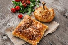 Schnellimbissostnationen Samsa und Hühnertrommelstock auf einer Servierplatte mit Koriander und Gemüse lizenzfreie stockfotos
