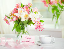 Schöner Blumenstrauß von Alstroemeria und Tasse Tee für das DA der Mutter Stockfotos
