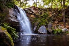 Schöner flüssiger Wasserfall in ein ruhiges und ruhiges Pool Lizenzfreies Stockfoto