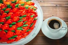 Schöner Hintergrund mit einer Schale heißem Kaffee mit Schaum und einem Geburtstagskuchen Stockbild