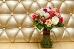 Schöner Hochzeitsblumenstrauß von den weißen und roten Rosen auf einem Goldhintergrund Lizenzfreie Stockbilder