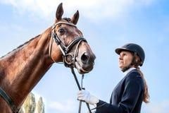 Schöner Jockeymädchenstand nahe bei ihrem Pferd Lizenzfreie Stockfotos