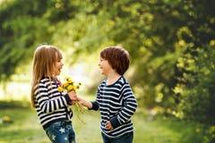 Schöner Junge und Mädchen in einem Park, Junge, der dem Mädchen Blumen gibt Stockbild