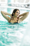 Schöner junger Brunette, der in einem Swimmingpool sich entspannt Stockfotos