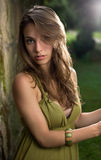 Schöner junger Brunette, der im grünen Kleid aufwirft. Lizenzfreie Stockfotografie