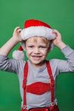Schöner kleiner Junge gekleidet wie Santa Claus-Helfer Weihnachtsniederlassung und -glocken Lizenzfreies Stockbild