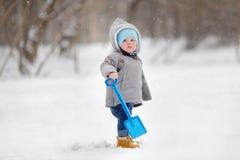 Schöner Kleinkindjunge, der mit Schnee spielt Stockfoto