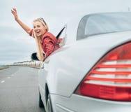Schöner lächelnder Damenblick heraus vom Autofenster auf der Autobahn Lizenzfreie Stockfotos