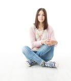 Schöner Mädchenjugendlicher, der auf Boden sitzt Stockfoto