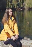 Schöner Mädchenstudent sitzt auf Geländer nahe dem Stadtteich in der Sonne Stockfotografie