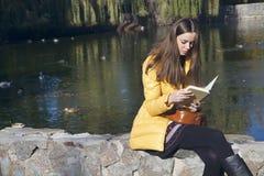 Schöner Mädchenstudent sitzt auf Geländer nahe dem Stadtteich in der Sonne Stockfoto