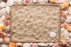 Schöner Rahmen von Seil- und Seeoberteilen auf dem Sand Stockfotografie