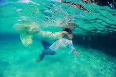 Schöner reizender Kuss der Braut und des Bräutigams Unterwasser Lizenzfreie Stockfotos