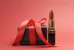 Schöner roter Luxuslippenstift mit dem Flugschreibergeschenk - horizontal. Stockbild