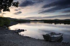 Schöner schwermütiger Sonnenaufgang über ruhigem See mit Boot auf Ufer Stockbild
