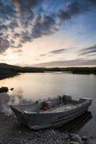 Schöner schwermütiger Sonnenaufgang über ruhigem See mit Boot auf Ufer Lizenzfreies Stockbild