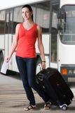 Sommerfrau mit Koffer und Reise etikettieren das Gehen am Busbahnhof Lizenzfreie Stockfotos
