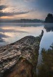 Schöner Sonnenaufgang über nebelhaftem See Lizenzfreies Stockfoto