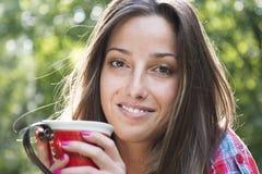 Schöner trinkender Kaffee der jungen Frau in einem Morgenpark Lizenzfreies Stockfoto
