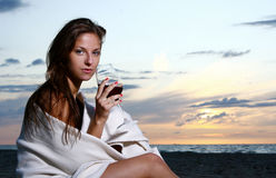 Schöner trinkender Wein der jungen Frau auf Strand Lizenzfreies Stockbild