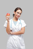 Schöner weiblicher Doktor mit einem Apfel Stockfotos