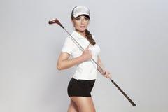 Schöner weiblicher Golfspieler auf dem grauen Hintergrund. Stockbild