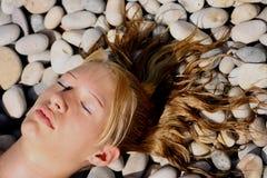 Schöner womans Kopf auf einem peble Strand. Stockbilder